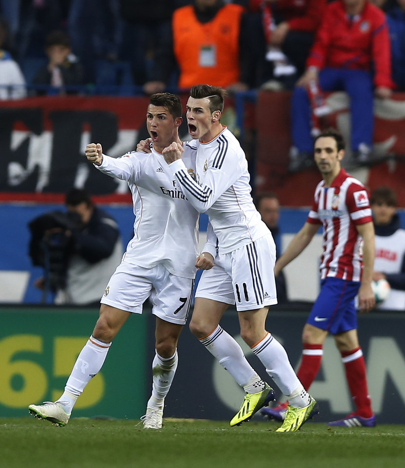 Photo - Real's Cristiano Ronaldo, left, celebrates his goal with teammate Gareth Bale, center, during a Spanish La Liga soccer match between Atletico de Madrid and Real Madrid at the Vicente Calderon stadium in Madrid, Spain, Sunday, March 2, 2014. (AP Photo/Andres Kudacki)