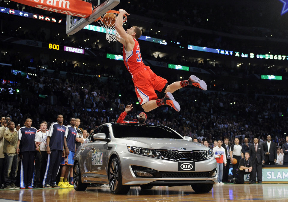 Los Angeles Clippers' Blake Griffin dunks over a car as teammate Baron Davis looks on from inside the car during the Slam Dunk Contest at the NBA basketball All-Star weekend, Saturday, Feb. 19, 2011, in Los Angeles.  (AP Photo/Mark J. Terrill)