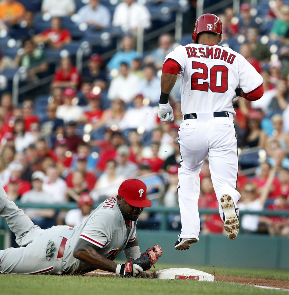 Photo - Washington Nationals' Ian Desmond (20) hops over a diving Philadelphia Phillies first baseman Ryan Howard (6) who got the out on Desomnd during the second inning of a baseball game at Nationals Park Tuesday, June 3, 2014, in Washington. (AP Photo/Alex Brandon)