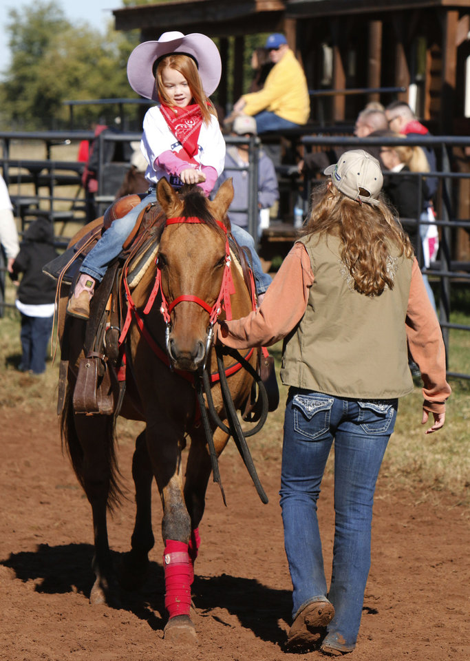 Volunteer Ashley Silvers guides five year old Kate Ivester on a horseback ride during the second annual Horseback Heroes for the Children of Oklahoma National Guardsmen in far southwest Oklahoma City, OK, Saturday, October 19, 2013,  Photo by Paul Hellstern, The Oklahoman