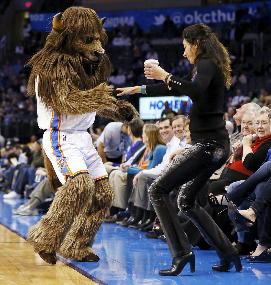Photo - Rumble the Bison dances with a fan during an NBA basketball game between the Oklahoma City Thunder and Charlotte Bobcats at Chesapeake Energy Arena in Oklahoma City, Monday, Nov. 26, 2012. Oklahoma City won, 114-69. Photo by Nate Billings , The Oklahoman