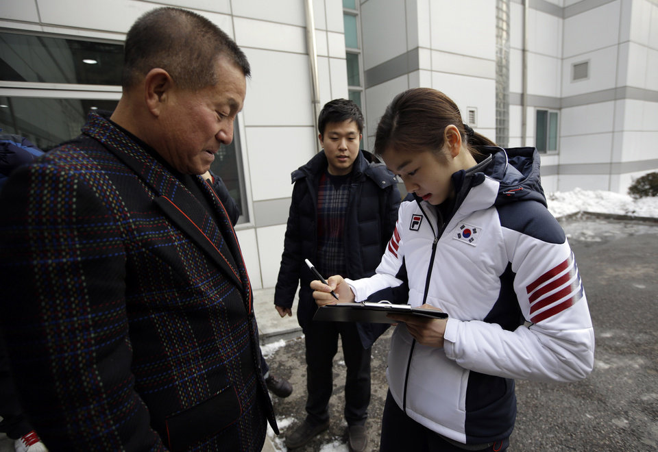 Photo - Kim Yuna, Vancouver gold medalist for the women's figure skating, signs her autograph for a fan prior to the inaugural ceremony of South Korean national team for the Sochi Winter Olympics in Seoul, South Korea, Thursday, Jan. 23, 2014. South Korea will send 64 athletes to Sochi which will be held from Feb. 7-23. (AP Photo/Lee Jin-man)