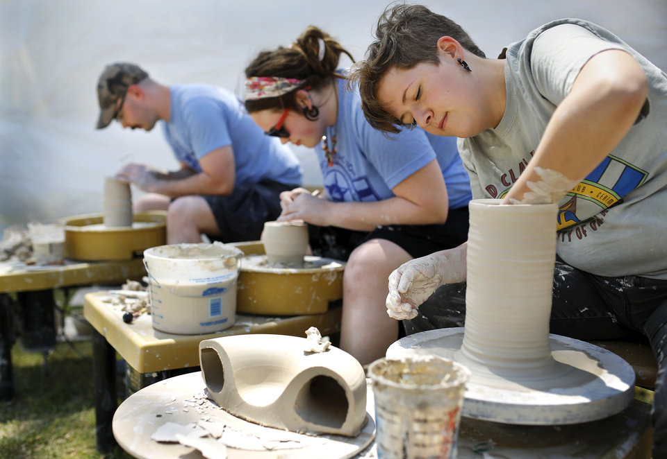 Photo -  Above: Members of Red Clay Faction, from foreground to background: Angela Rodriguez, Olivia Egan and Dave Stevens — all students from University of Oklahoma's ceramics program — give a pottery demonstration Wednesday at the Festival of the Arts in downtown Oklahoma City.    Jim Beckel -  THE OKLAHOMAN