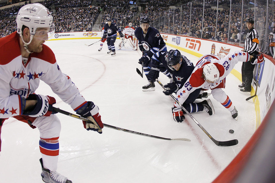Photo - Washington Capitals' Karl Alzner (27) and Jay Beagle (83) fight for the puck in the corner with Winnipeg Jets' Derek Meech (7) and Alexander Burmistrov (8) during the second period of an NHL hockey game in Winnipeg, Manitoba, on Thursday, March 21, 2013. (AP Photo/The Canadian Press, John Woods)