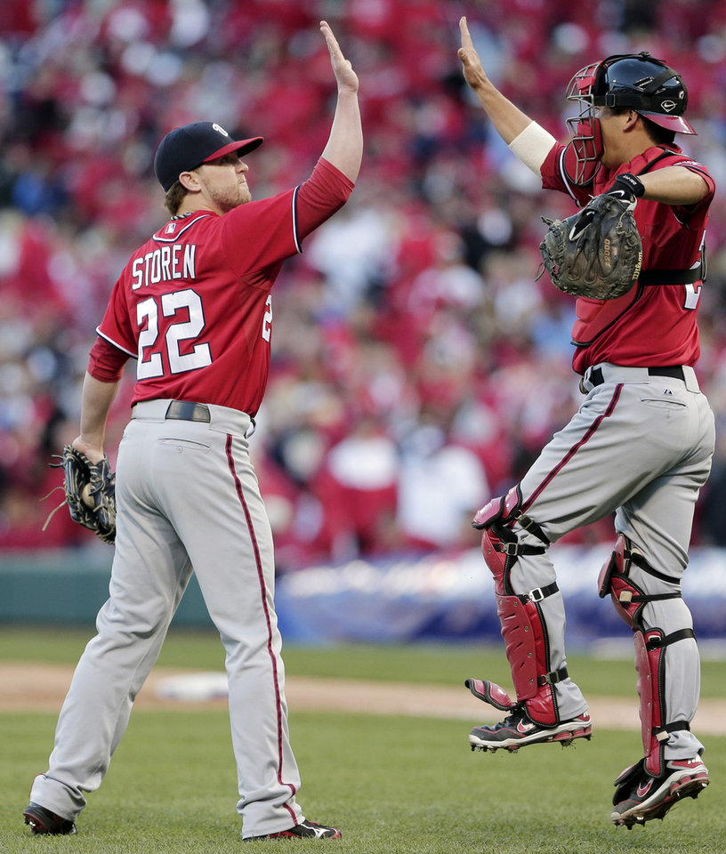 Washington Nationals relief pitcher Drew Storen (22) and catcher Kurt Suzuki celebrate their 3-2 win over the St. Louis Cardinals in Game 1 of the National League division baseball series, Sunday, Oct. 7, 2012, in St. Louis. (AP Photo/Charlie Riedel)