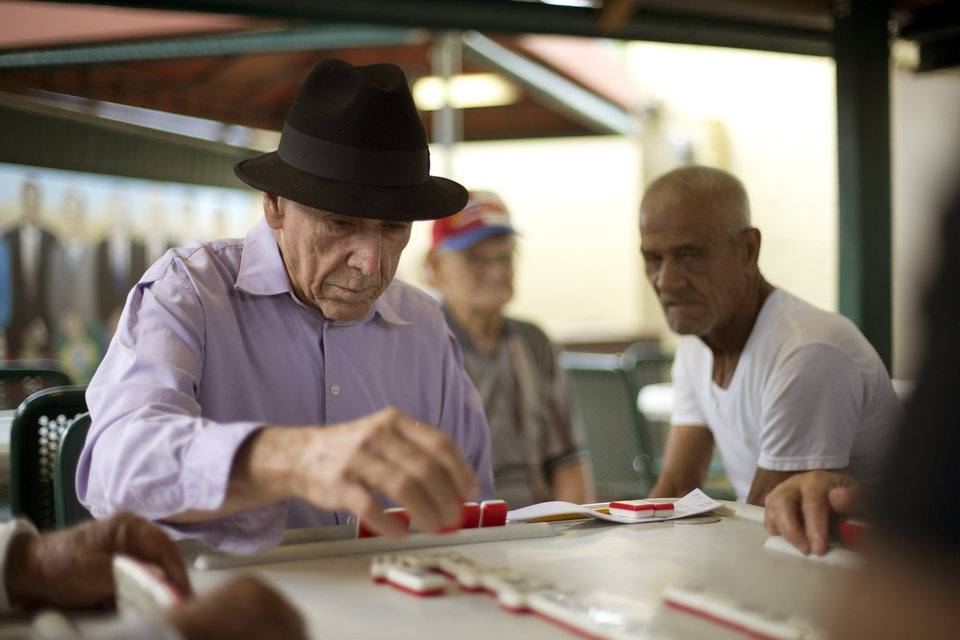 Photo - This May 2, 2014 photo shows men playing dominoes on Calle Ocho (Eighth Street) in Miami's Little Havana. Once a refuge for Cuban exiles rekindling the tastes and sounds a lost home, today Miami's Little Havana is a mosaic of cultures and a popular tourist destination. (AP Photo/J Pat Carter)