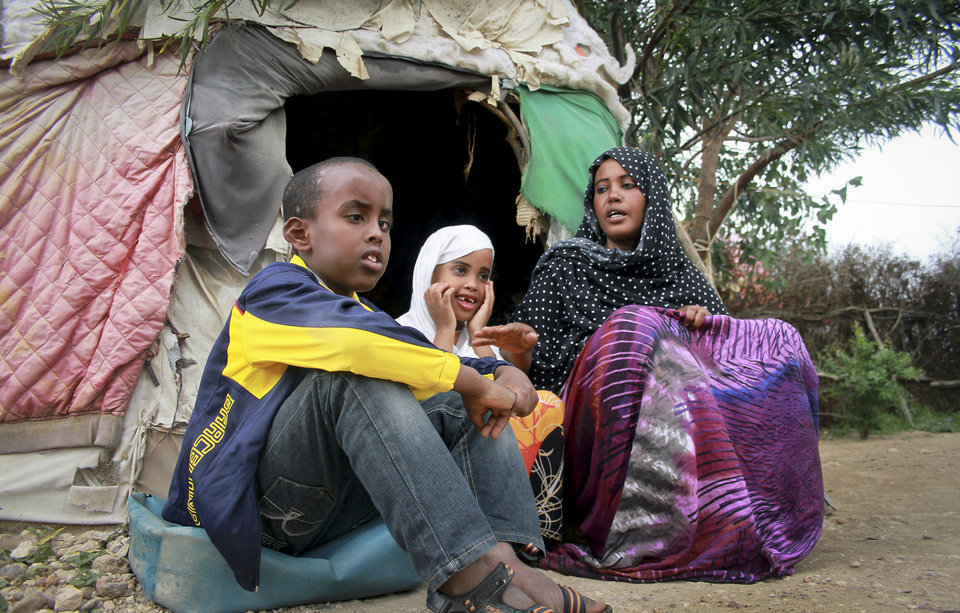 Photo - In this photo taken Sunday, April 27, 2014, Ubah Mohammed Abdule, 33, right, sits with her son Abdullahi Yusuf Ahmed, 8, left, and daughter Neshad Yusuf Ahmed, 5, center, outside her hut in the Shedder refugee camp near the town of Jigjiga, in far eastern Ethiopia. The Somali mother's home is a small shelter with a frame of sticks covered by ragged blankets on the dusty grounds of a refugee camp but it was to her that her 15-year-old son Yahya Abdi wanted to travel to on an impossible journey as a stowaway on a plane from California. (AP Photo/Elias Asmare)