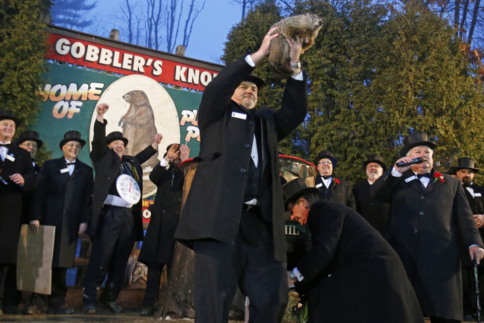 Photo - Punxsutawney Phil is held by handler John Griffiths after emerging from his burrow Sunday, Feb. 2, 2014, on Gobblers Knob in Punxsutawney, Pa., to see his shadow and forecast six more weeks of winter weather. This year's Groundhog Day celebration marks a winter that has brought extreme cold to stretches of the United States wholly unaccustomed to it, as well as a snow and ice storm that paralyzed Atlanta and other Southern cities. (AP Photo/Gene J. Puskar)