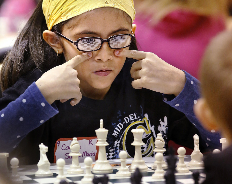 Photo - Camila Santa Maria, a third-grader at Parkview Elementary School, concentrates on her next move on  Saturday at Carl Albert High School. Students in the Midwest City-Del City School District matched wits and strategy with each other during the district's annual elementary school chess tournament. More than 100  students competed in the event. Some players were as young as 6 years old. PHOTOs BY JIM BECKEL, THE OKLAHOMAN