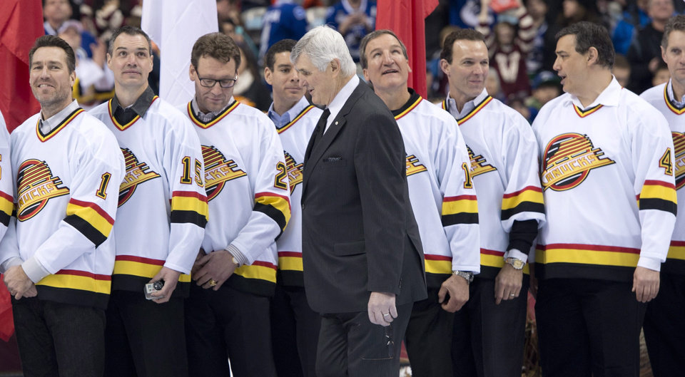 Photo - Pat Quinn walks past former members of the Vancouver Canucks before the NHL Heritage Classic hockey game between the Canucks and the Ottawa Senators in Vancouver, British Columbia,, on Sunday, March 2, 2014. (AP Photo/The Canadian Press, Jonathan Hayward)