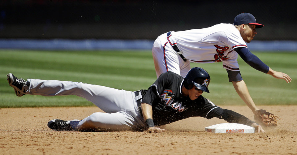 Photo - Miami Marlins' Christian Yelich, left, is out at second base as Atlanta Braves shortstop Andrelton Simmons, right, watches his throw to first as Marlins' Marcell Ozuna grounds into a force out in the eighth inning of a baseball game, Wednesday, April 23, 2014, in Atlanta. (AP Photo/David Goldman)