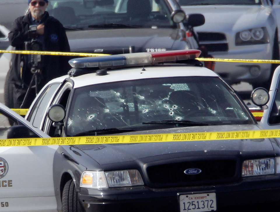 FILE - This Feb. 7, 2013 file photo shows a bullet-riddled Los Angeles Police vehicle in Corona, Calif after suspect, former Los Angeles police officer Christopher Dorner, shot at two LAPD officers in the vehicle who were sent to Corona to protect someone Dorner threatened in a rambling online manifesto. (AP Photo/Nick Ut, File)