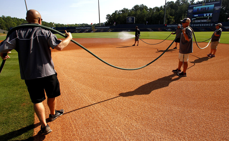 Photo - In this May 21, 2014 photo, the grounds crew sprays the infield before a game at the Southeastern Conference NCAA college baseball tournament in Hoover, Ala. (AP Photo/Butch Dill)
