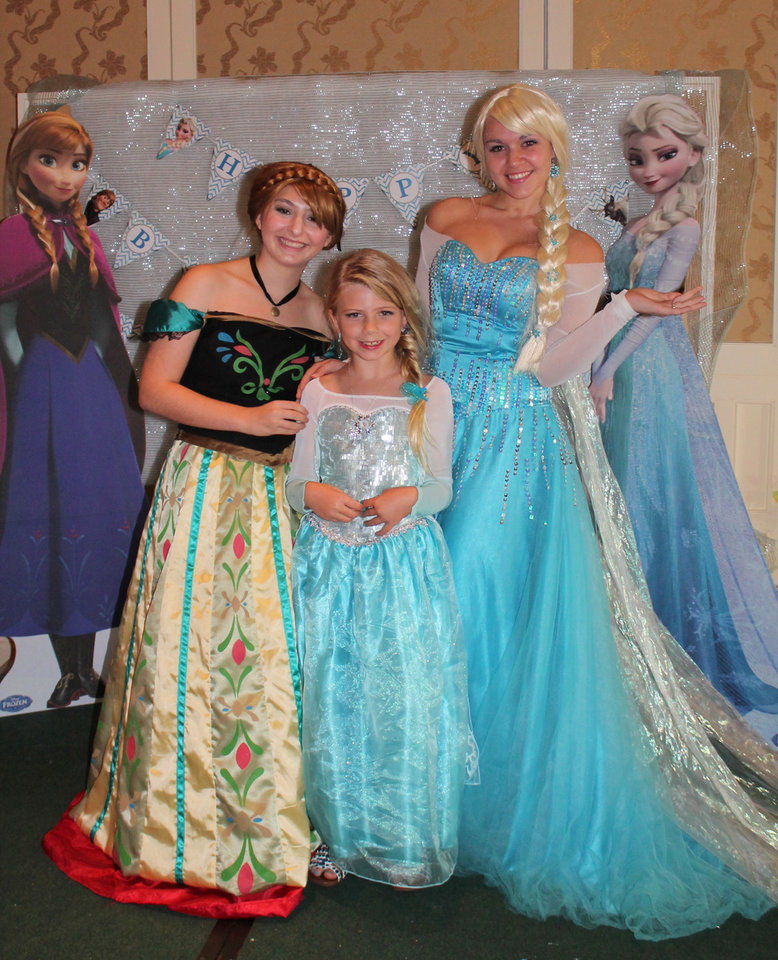 "Photo - In this Saturday, May 31 photo, Caroline Calder poses at her 9th birthday party with Devin Tupler and Hannah Solimini, performers portraying princesses Elsa and Anna from the movie 'Frozen.' Caroline's family hired the princesses and decorated their home in a ""Frozen"" theme for the party. The Disney movie has proven extremely popular, leading to sold-out fan merchandise and long lines at Disney World to meet characters from the movie. (AP Photo/Kristin Calder)"