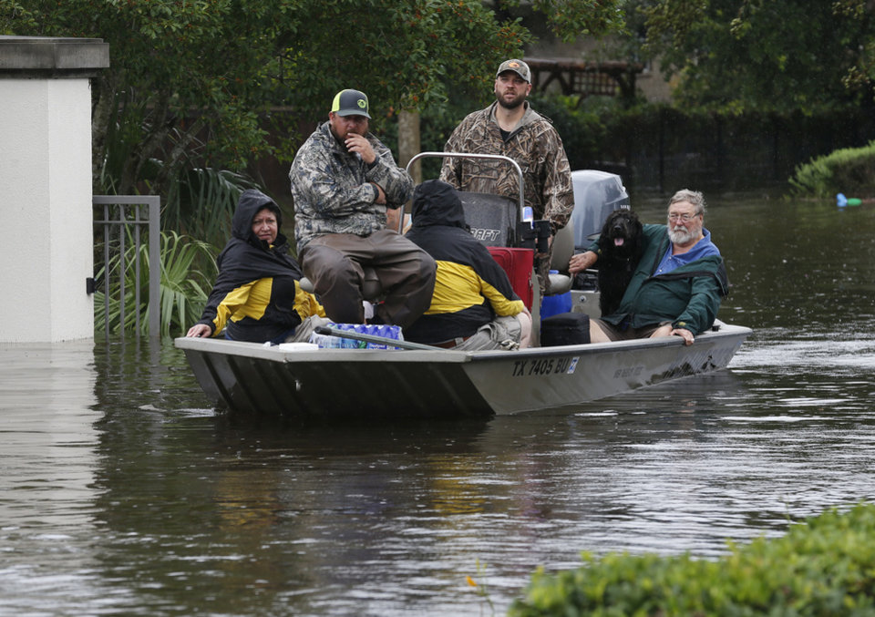 Photo - Volunteers bring a load of passengers rescued from the opposite bank of Clear Creek to FM 518 in League City, Texas, Sunday, Aug. 27, 2017. (Kevin M. Cox/The Galveston County Daily News via AP)