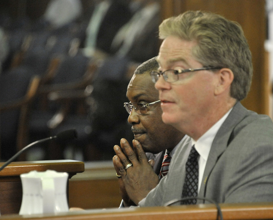 Photo - Rep. Thomas Stallworth III, left, D-Detroit, left, assumes a prayerful position while colleague Rep. John Walsh, R-Livonia speaks tothe senate committee on Government Operations on the bills associated with easing Detroit's bankruptcy in Lansing, Mich., Tuesday, June 3, 2014. Michigan's Senate approved on Tuesday spending $195 million to help prevent steeper cuts in Detroit retiree pensions, linking the state with a deal designed to shield valuable city-owned art from being sold and resolve the largest public bankruptcy in U.S. history. The  (AP Photo/Detroit News, Dale G. Young) DETROIT FREE PRESS OUT; HUFFINGTON POST OUT. MANDATORY CREDIT