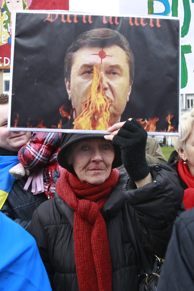 Photo - A Ukrainian woman shows a portrait of Ukrainian President Viktor Yanukovych during a protest in front of the European Parliament building in Brussels, Wednesday, Feb. 19, 2014. The deadly clashes in Ukraine's capital have drawn sharp reactions from Washington, sparked a rapidly growing push for European Union sanctions and led to a Kremlin statement blaming Europe and the West. (AP Photo/Yves Logghe)