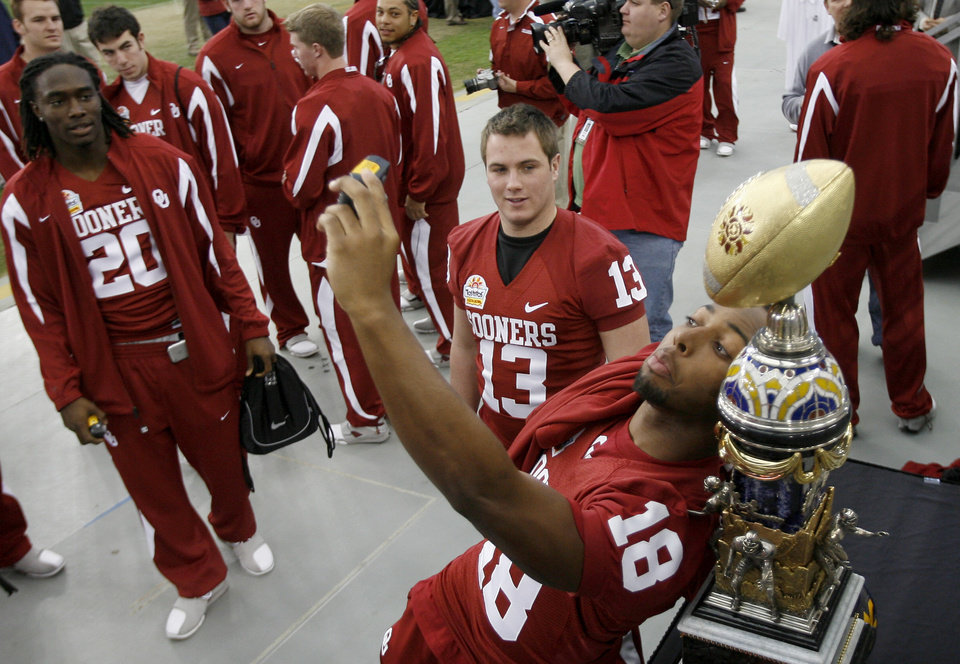 Photo - OU's Cortney Carter, right, takes his photo with the Fiesta Bowl trophy as Mike Knall, center, and Quinton Carter watch during media day at the University of Phoenix Stadium in Glendale, Ariz., on Monday, Dec. 31, 2007.  The University of Oklahoma (OU) college football team will play West Virginia University in the Fiesta Bowl on Jan. 2, 2008.  BY BRYAN TERRY, THE OKLAHOMAN ORG XMIT: KOD