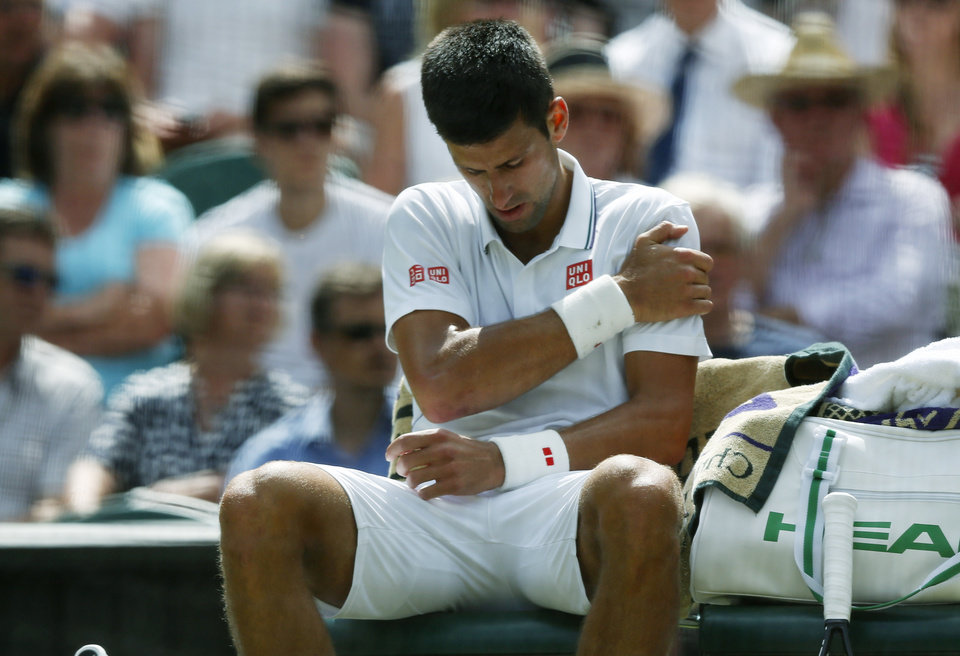 Photo - Novak Djokovic of Serbia grimaces in pain and holds his shoulder during the men's singles match against Gilles Simon of France at the All England Lawn Tennis Championships in Wimbledon, London, Friday, June 27, 2014. (AP Photo/Sang Tan)