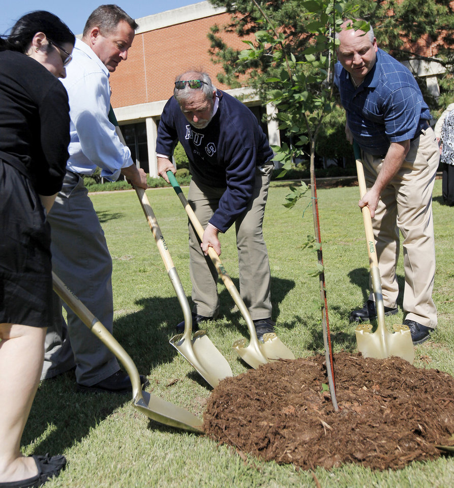 From left, Sarri Singer, Glenn Radalinsky, Charlie Kaczorowski and Tom Canavan shovel the last bits of soil on a seedling from the Oklahoma City Survivor Tree during the 4/19 - 9/11 Survivor Tree dedication at Oklahoma Christian University. Singer is a survivor of a terrorist attack in Israel and the director of One Heart, an organization that brings together survivors of terrorist attacks. Radalinsky is a ground zero rescue worker who because of injuries suffered during the rescue and recovery is now retired disabled from the Nassau County Police Department. Kaczorowski is a survivor of the 1993 bombing of the World Trade Center, survivor of the Sept. 11, 2001, terrorist attacks and was the site supervisor for recovery and cleanup at ground zero for 10 months. Canavan is a 9/11 survivor who dug himself out of the north tower of the World Trade Center. Photos by Nate Billings, The Oklahoman