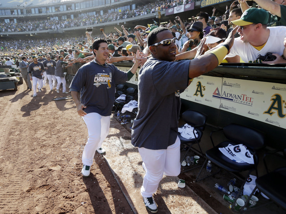 Photo -   Oakland Athletics' Yoenis Cespedes, right, and Tommy Milone celebrate with fans after their 12-5 win over the Texas Rangers in a baseball game, Wednesday, Oct. 3, 2012 in Oakland, Calif. The A's clinched the AL West title with the win. (AP Photo/Marcio Jose Sanchez)