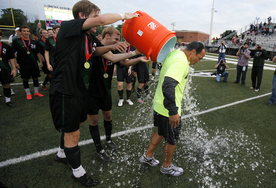 Norman North coach Geo Claros is dunked by his team after winning the boys 6A state championship soccer game over Tulsa Union in Newcastle, Okla., Saturday, May 12, 2012. Photo by Bryan Terry, The Oklahoman