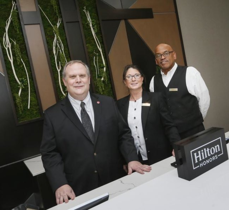 Photo -  From left, Patrick Whyatt, general manager, Jammia Cline, front office manager, and Roscoe Buckner, guest service agent, are shown at the front desk of the Embassy Suites hotel at 3233 Northwest Expressway. [NATE BILLINGS/THE OKLAHOMAN]