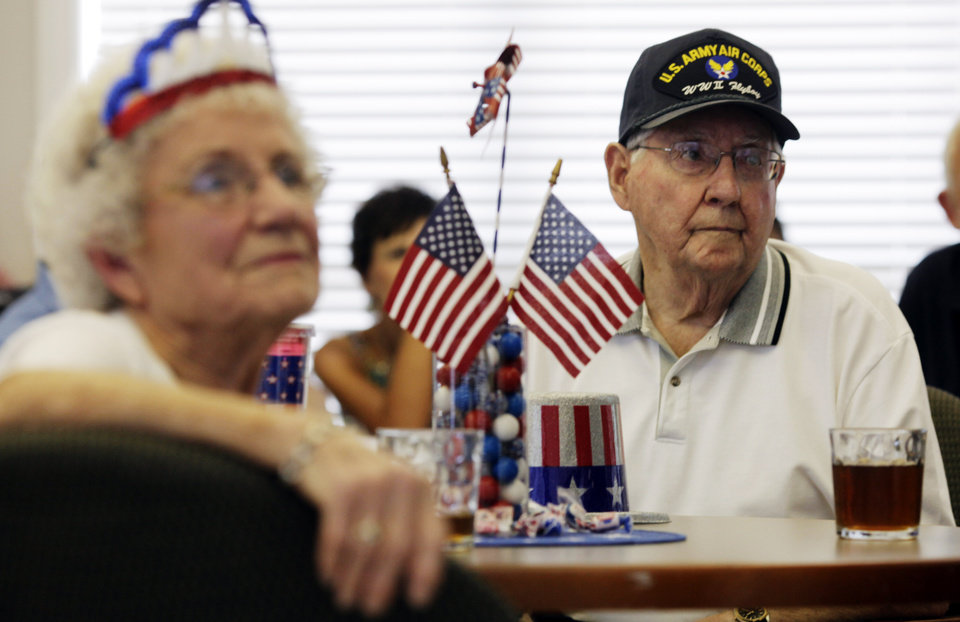 Photo - Margaret Martin (left) and husband John Martin (right), a World War II veteran of the Army Air Force, watch a picture slideshow at John's 90th birthday party on July 7, 2013. John Martin received three metals he had been awarded in World War II but had not received until 2013. Photo by KT KING, The Oklahoman