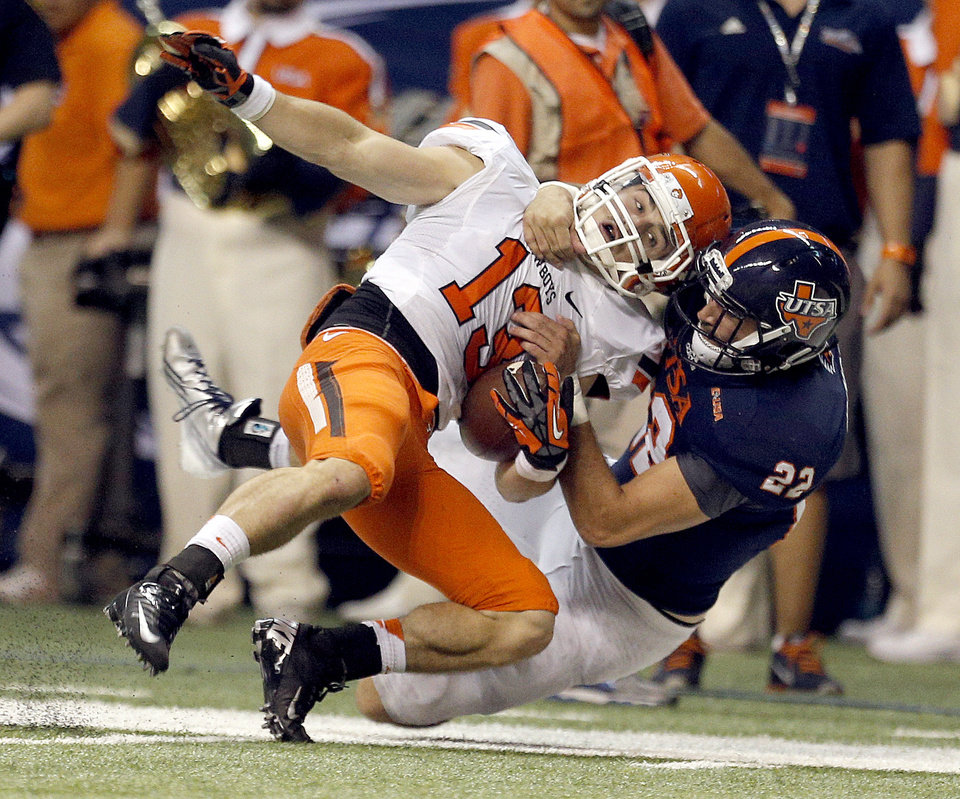 Photo - Oklahoma State's David Glidden (13) is brought down by UTSA's Nic Johnston (22) during the first half of a college football game between the University of Texas at San Antonio Roadrunners (UTSA) and the Oklahoma State University Cowboys (OSU) at the Alamodome in San Antonio, Saturday, Sept. 7, 2013.  Photo by Sarah Phipps, The Oklahoman