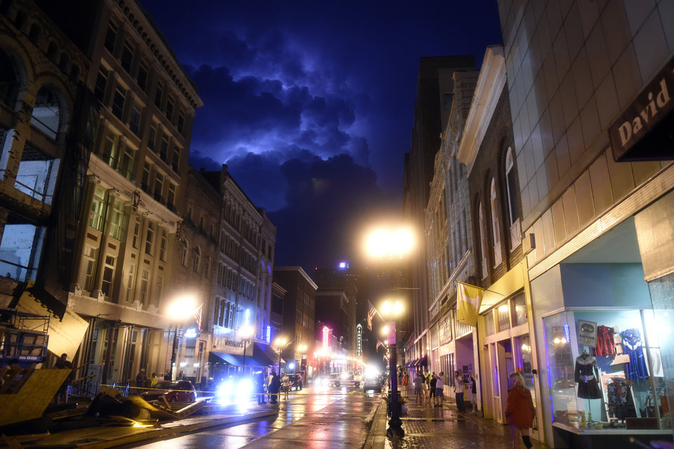 Photo - Lightning strikes behind a bank of storm clouds in Knoxville, Tenn., on Sunday, July 27, 2014. Authorities say powerful storms crossing east Tennessee have destroyed 10 homes and damaged others. (AP Photo/The Knoxville News Sentinel, Saul Young)