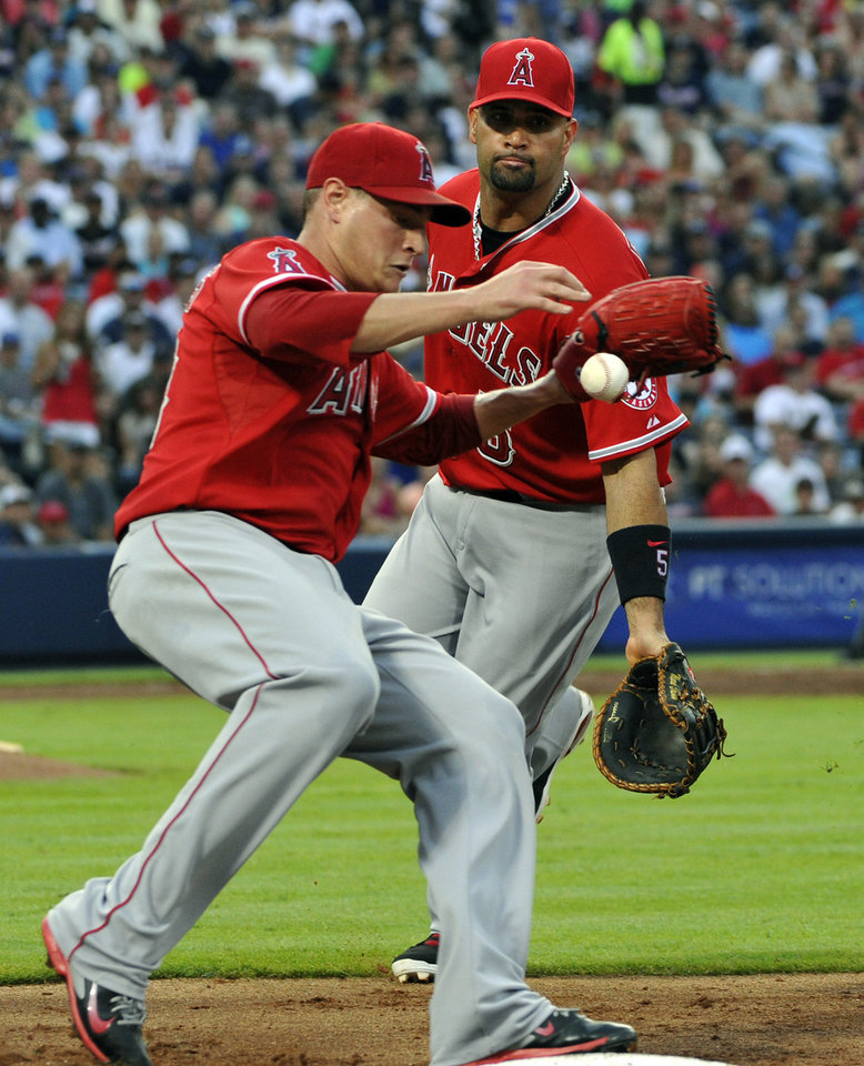 Photo - Los Angeles Angels pitcher Garrett Richards, left, is charged with a missed catch error from first baseman Albert Pujols, right, on a ground ball by Atlanta Braves' Jason Heyward during the third inning of a baseball game on Saturday, June 14, 2014, in Atlanta. (AP Photo/David Tulis)