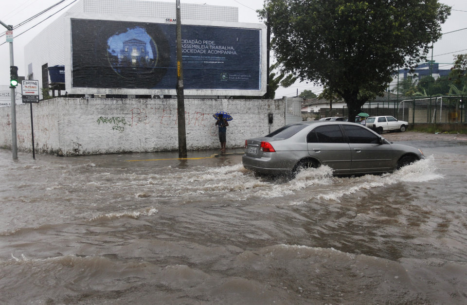 Photo - A vehicle makes its way down a flooded street after heavy rain storms in Recife, Brazil, Thursday, June 26, 2014. The World Cup soccer match between the USA and Germany will be played at the Arena Pernambuco in Recife today.  (AP Photo/Petr David Josek)