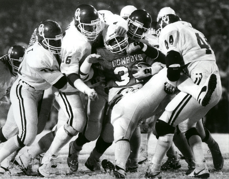 Photo - The Oklahoma defense puts the skids on a rushing attempt by OSU fullback Will Timmons during the Bedlam college football game on Nov. 30, 1985. Staff Photo by Paul Hellstern