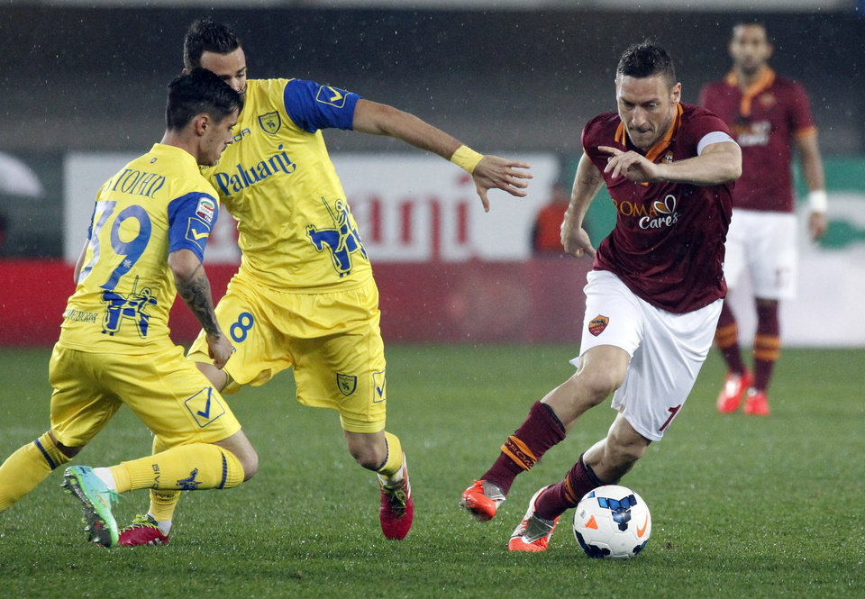 Photo - AS Roma's Francesco Totti, right, is chased by Chievo's Adrian Stoian, left, of Romania, and teammate Ivan Radovanovic, of Serbia, during a Serie A soccer match at Bentegodi stadium in Verona, Italy, Saturday, March 22, 2014. (AP Photo/Felice Calabro')