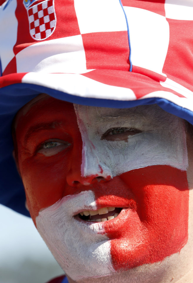 Photo - A soccer fan with his face painted in red and white, the Croatian national soccer team's colors, waits to enter Itaquerao Stadium to watch the World Cup opening match, between Brazil and Croatia of group A, in Sao Paulo, Brazil, Thursday, June 12, 2014.  (AP Photo/Julio Cortez)