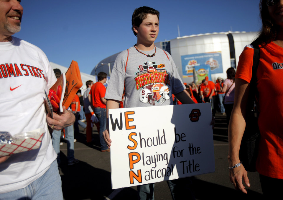 Photo - Genson Streets, 15, and his parents, Don and Cheryl Streets, of Bartlesville, Okla., walk outside the stadium before the Fiesta Bowl between the Oklahoma State University Cowboys (OSU) and the Stanford Cardinal at the University of Phoenix Stadium in Glendale, Ariz., Monday, Jan. 2, 2012. Photo by Bryan Terry, The Oklahoman