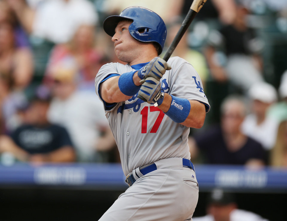 Photo - Los Angeles Dodgers' A.J. Ellis follows the flight of his sacrifice fly to drive in a run against the Colorado Rockies in the fourth inning of a baseball game in Denver on Thursday, July 3, 2014. (AP Photo/David Zalubowski)