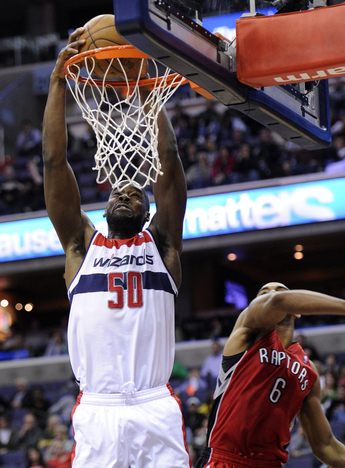 Photo - Washington Wizards center Emeka Okafor (50) dunks over Toronto Raptors guard Alan Anderson (6) during the second half of an NBA basketball game, Sunday, March 31, 2013, in Washington. The Wizards won 109-92. (AP Photo/Nick Wass)