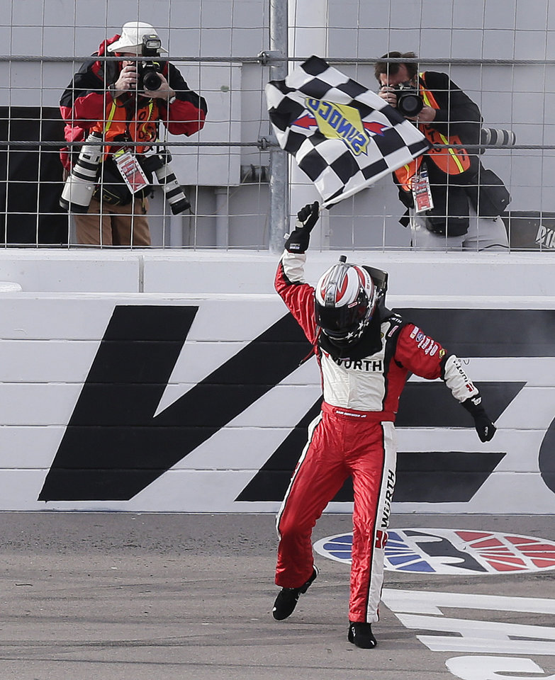 Sam Hornish Jr. waves the checkered flag at the finish line after his victory in the NASCAR Nationwide Series auto race, Saturday, March 9, 2013, in Las Vegas. (AP Photo/Julie Jacobson)