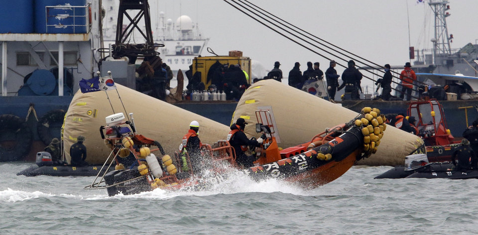 Photo - Searchers and divers look for people believed to have been trapped in the sunken ferry boat Sewol near the buoys which were installed to mark the vessel in the water off the southern coast near Jindo, south of Seoul, South Korea, Tuesday, April 22, 2014. One by one, coast guard officers carried the newly arrived bodies covered in white sheets from a boat to a tent on the dock of this island, the first step in identifying a sharply rising number of corpses from a South Korean ferry that sank nearly a week ago. (AP Photo/Lee Jin-man)