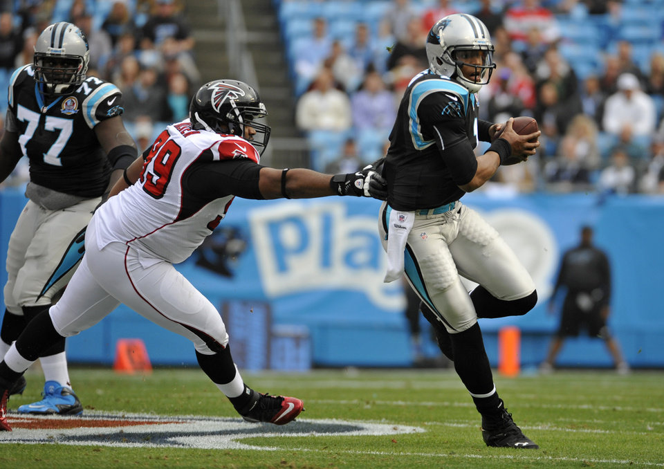Carolina Panthers\' Cam Newton (1) scrambles for a gain as Atlanta Falcons\' Vance Walker (99) chases during the first half of an NFL football game in Charlotte, N.C., Sunday, Dec. 9, 2012. (AP Photo/Rainier Ehrhardt)