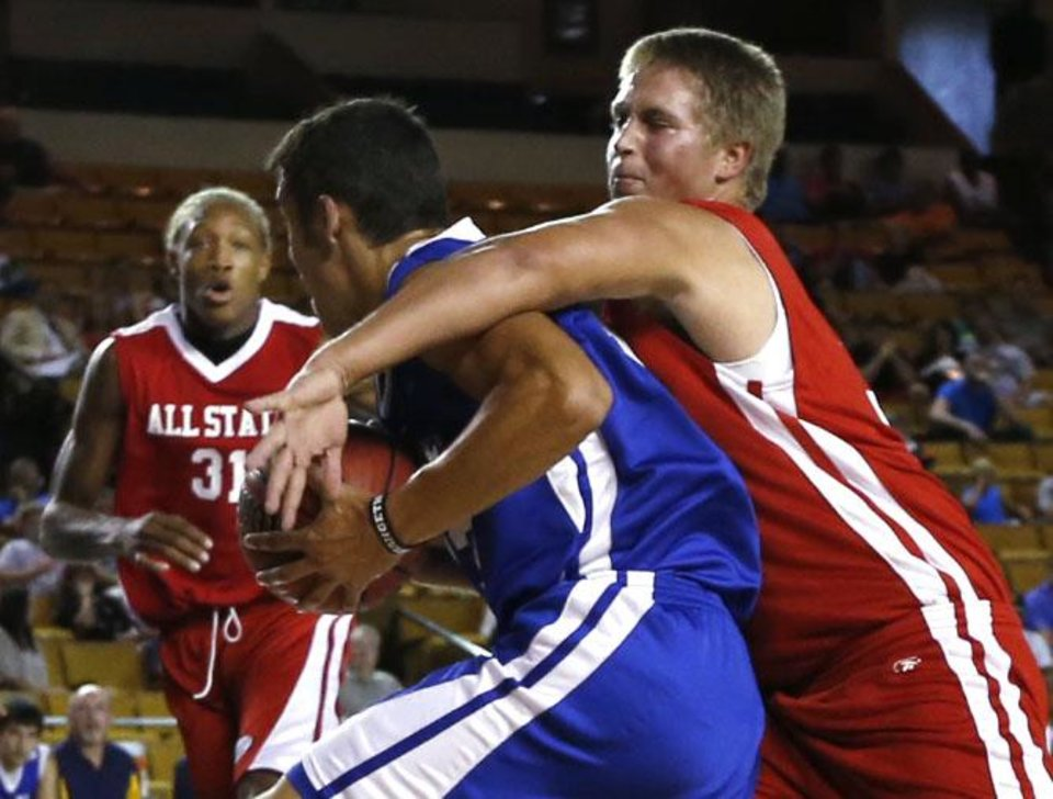 Small East\'s Jeylyn Sharpe (center) of Ketchum is wrapped up by the West\'s Seth Overstreet (right) of Laverne, as the West\'s Tony Aska (left) of Coyle, looks on, during the Boys All-State basketball game, at the Mabee Center, on Thursday, Aug. 1, 2013. CORY YOUNG/Tulsa World ORG XMIT: DTI1308012041190954