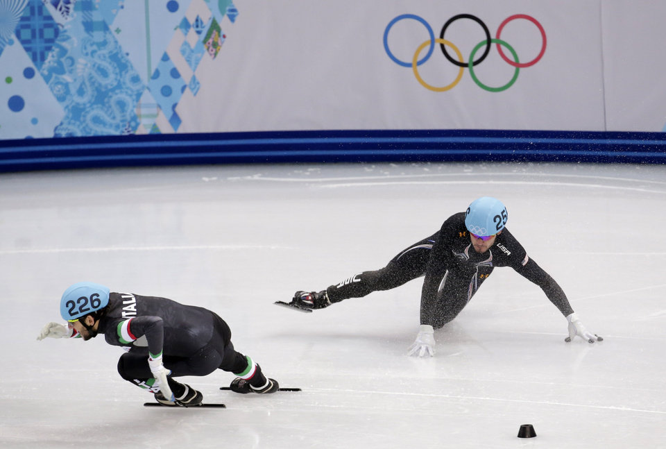Photo - Eduardo Alvarez of the United States, right, crashes out as Yuri Confortola of Italy rounds the corner in a men's 500m short track speedskating heat at the Iceberg Skating Palace during the 2014 Winter Olympics, Tuesday, Feb. 18, 2014, in Sochi, Russia. (AP Photo/Bernat Armangue)