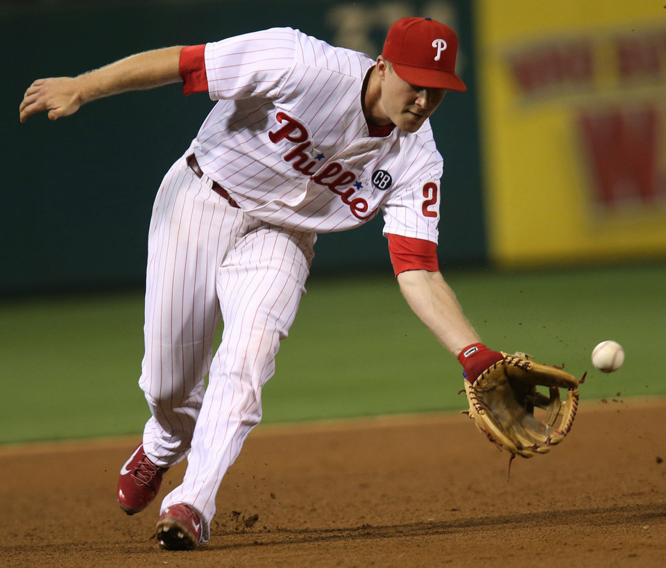 Photo - Philadelphia Phillies Cody Asche fields a grounder by St. Louis Cardinals' Kolten Wong for an out in the fourth inning of a baseball game, Friday, Aug. 22, 2014, in Philadelphia. (AP Photo/Laurence Kesterson)