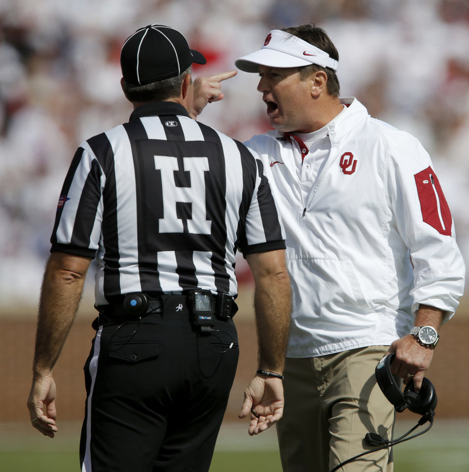 Photo - Oklahoma coach Bob Stoops argues with an official during a college football game between the University of Oklahoma Sooners (OU) and the West Virginia Mountaineers (WVU) at Gaylord Family-Oklahoma Memorial Stadium in Norman, Okla., on Saturday, Oct. 3, 2015. Photo by Bryan Terry, The Oklahoman