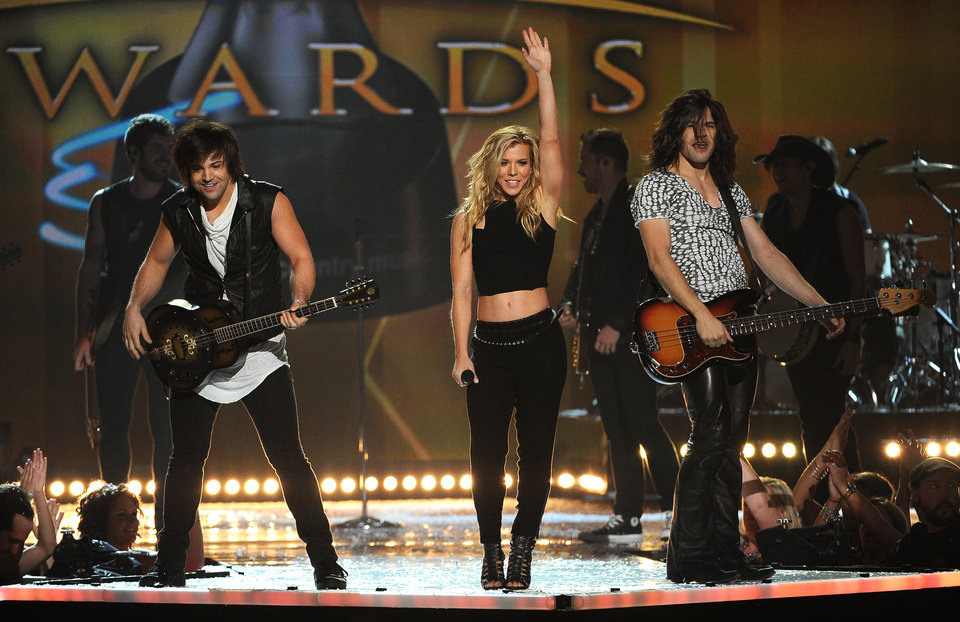 Photo - Neil Perry, left, Kimberly Perry and Reid Perry, of the musical group The Band Perry, perform at the 49th annual Academy of Country Music Awards at the MGM Grand Garden Arena on Sunday, April 6, 2014, in Las Vegas. (Photo by Chris Pizzello/Invision/AP)
