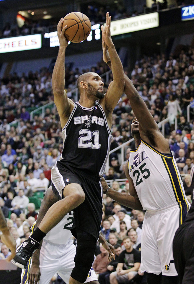 Photo - San Antonio Spurs forward Tim Duncan (21) shoots as Utah Jazz center Al Jefferson (25) defends in the first quarter during an NBA basketball game, Wednesday, Dec. 12, 2012, in Salt Lake City. (AP Photo/Rick Bowmer)