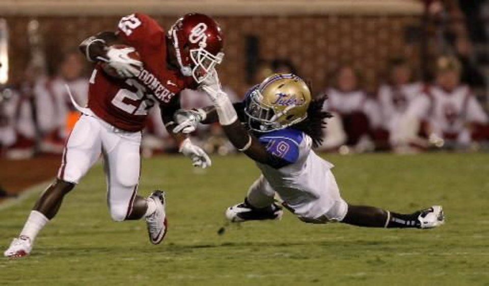 Photo - Oklahoma's Roy Finch (22) fights off Tulsa's Milton Howell (19) during the college football game between the University of Oklahoma Sooners ( OU) and the Tulsa University Hurricanes (TU) at the Gaylord Family-Memorial Stadium on Saturday, Sept. 3, 2011, in Norman, Okla. Photo by Bryan Terry, The Oklahoman ORG XMIT: KOD