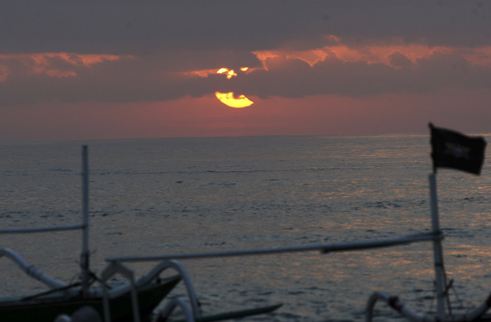 Photo - A partial solar eclipse is seen through clouds over Sanur beach, Bali, Indonesia, Friday, May 10, 2013. (AP Photo/Firdia Lisnawati)