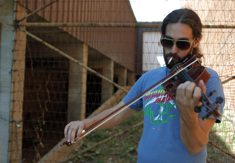Photo - Jon Knudson, of the Damn Quails, practices before a show during the Woody Guthrie Folk Festival in Okemah, Okla., Thursday, July 12, 2012.  Photo by Garett Fisbeck, The Oklahoman